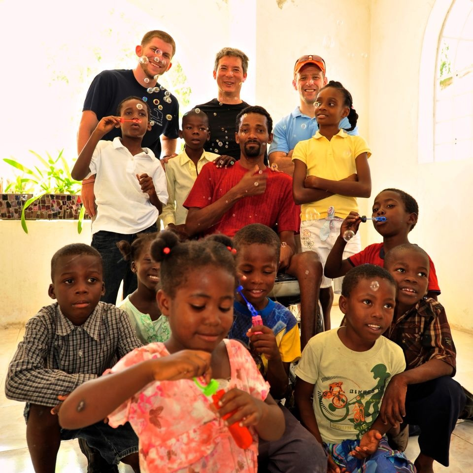 Andrew (back, right) and fellow Team Broken Earth members with some of the local children in Port-au-Prince, Haiti