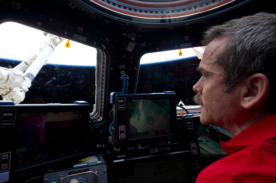 At the controls of Canadarm2, inside the Cupola of the ISS, February 2013. Photo: NASA