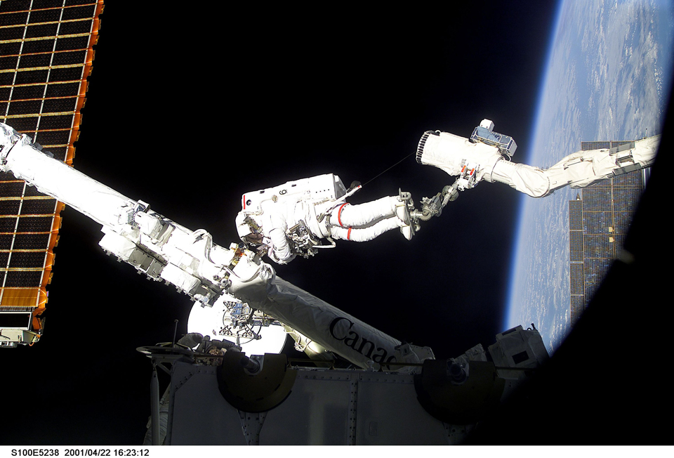 Chris on a spacewalk to install Canadarm 2 on the ISS, with feet attached to Canadarm. Photo: NASA