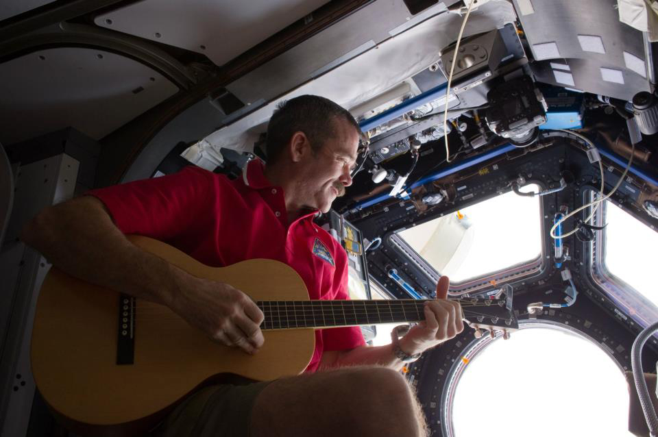 Chris strumming his guitar aboard the ISS, December 2012. Photo: NASA