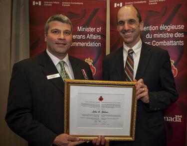 John (left) receives his commendation from then-Minister of Veterans Affairs Steven Blaney, 2012